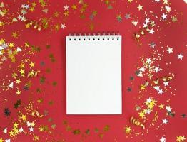 folha branca em branco do caderno sobre um fundo vermelho com confetes espalhados pelo conceito de fotografia de conceito de educação de férias foto
