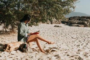 jovem marroquina com roupas modernas sentada na praia lendo um livro durante um dia ensolarado com espaço de cópia inspirador e tema de relaxamento com tons coloridos foto