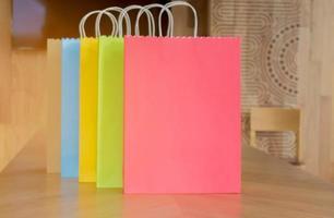 sacolas de papel coloridas em mesas de madeira para mulheres conceito de moda e compras foto