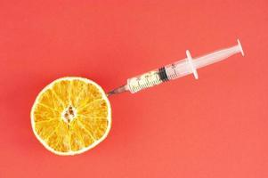 uma laranja seca com seringa presa em fundo vermelho foto