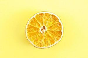 um pedaço de laranja seca em fundo amarelo foto
