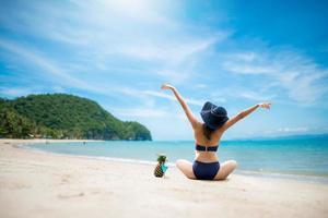mulher sexy de biquíni azul pulando na praia foto