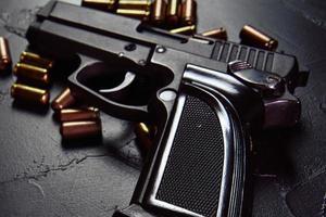 pistola preta com cartuchos na mesa foto