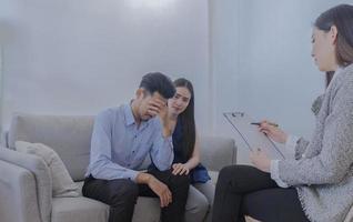 jovem casal asiático consulta um psiquiatra por causa de uma condição em pacientes com transtorno depressivo maior, conceito de cuidados de saúde foto