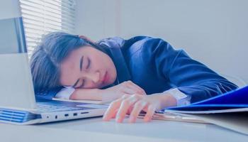 retrato de uma jovem mulher de negócios asiática dormindo na mesa, cansado foto