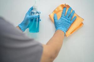 limpar a parede de azulejos com pano e álcool na cozinha em casa para proteger o covid 19 coronavírus foto