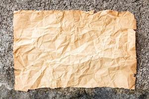o velho papel amassado na parede de cimento foto