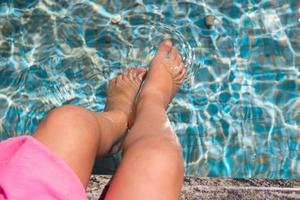 menina sentada na beira da piscina foto