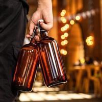 homem segurando dois copos de cerveja na mão, vista traseira foto