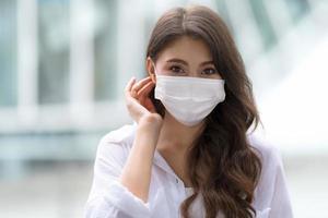 retrato de mulher jovem com uma carinha sorridente usando máscara facial protetora caminha em uma cidade foto