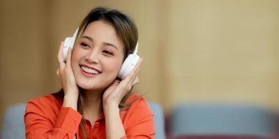 retrato de uma jovem mulher bonita curtindo música com uma carinha sorridente, sentado em um escritório criativo ou um café foto