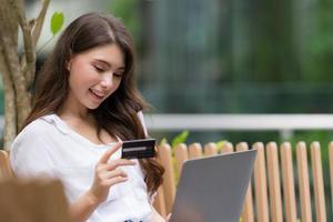 jovem sentada em uma cadeira no parque da cidade usando laptop foto