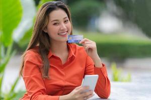 retrato ao ar livre de uma mulher feliz segurando um cartão de crédito foto