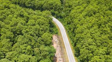 vista aérea superior de uma estrada provincial passando por um fundo de floresta foto