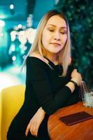 linda garota de vestido preto em restaurante foto