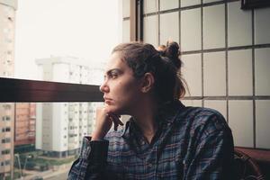 mulher preocupada olhando da janela de seu apartamento foto