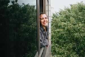 mulher sorrindo para a janela durante um dia de primavera foto