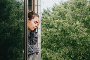 mulher preocupada perto da janela da cidade durante um dia de primavera foto
