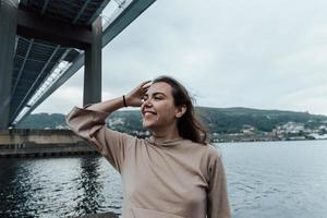 mulher sorrindo enquanto desvia o olhar debaixo de uma ponte foto
