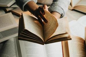 um par de mãos lendo um livro antigo foto