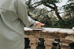 close-up de uma mão sobre um monte de livros foto