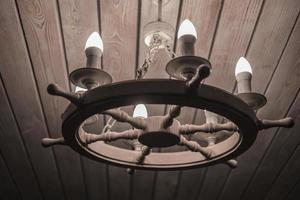 lâmpada com lustre de lâmpadas em forma de uma roda de teto de madeira foto