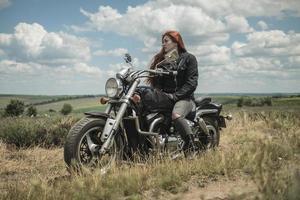 a garota motoqueira ruiva está sentada em um campo de motocicleta em um prado e nuvens foto