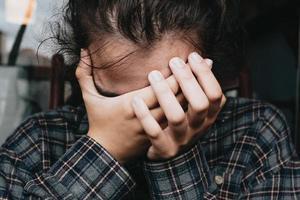 mulher preocupada com as mãos no rosto foto