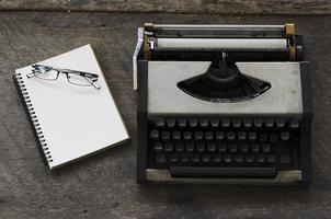 máquina de datilografia antiga e óculos com notas de livro no fundo de madeira foto