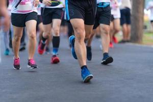 maratona correndo pessoas pés na estrada sob a luz do amanhecer foto