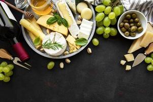 vários tipos de queijos, uvas, vinhos e petiscos foto