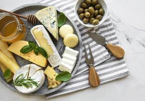 vários tipos de queijo, uvas, mel e salgadinhos em um fundo de concreto preto foto