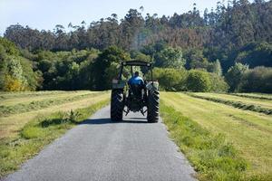 cena de um velho trator visto de trás em uma estrada em uma área rural foto