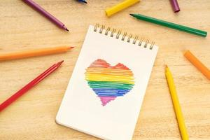 caderno com desenho em forma de coração de bandeira de arco-íris lgbt e canetas hidrográficas na mesa de madeira foto