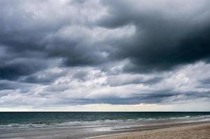 céu escuro dramático e nuvens tempestuosas sobre o mar foto