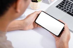 homem usando uma simulação de tela em branco de smartphone na mesa de escritório branca foto