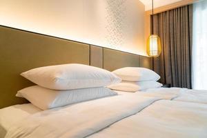 decoração de travesseiro branco na cama em um quarto de hotel resort foto