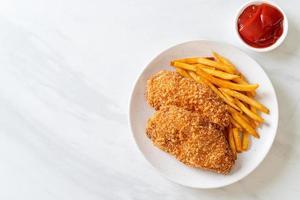 Filé de peito de frango frito com batata frita e ketchup foto