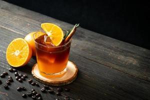 um copo de café preto americano gelado e uma camada de suco de laranja e limão decorado com alecrim e canela foto