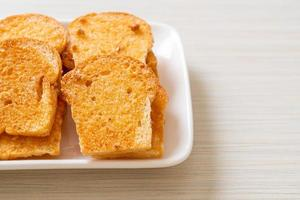 pão crocante assado com manteiga e açúcar em um prato foto