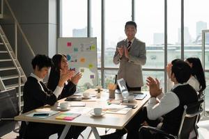 Gerente executivo asiático de meia-idade batendo palmas com uma equipe de negócios multirracial para o sucesso de um novo projeto na sala de reuniões do escritório foto