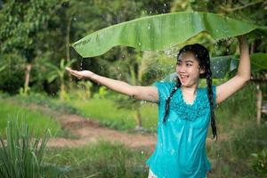 imagem borrada retrato de uma jovem asiática com cabelo preto segurando uma folha de bananeira na chuva no fundo do jardim verde foto