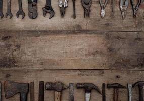 coleção de ferramentas manuais antigas para trabalhar madeira em uma bancada de madeira velha foto