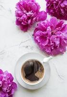 flores de peônia rosa e xícara de café foto