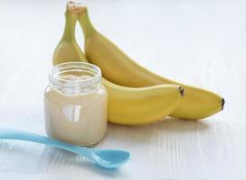 pote de purê de banana e bananas foto