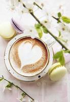 café com padrão em forma de coração e sobremesas de macaroons doces foto