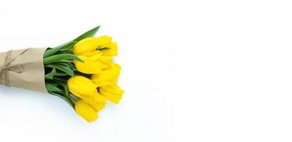 buquê de tulipas amarelas embrulhadas em papel artesanal em fundo branco com espaço de cópia foto