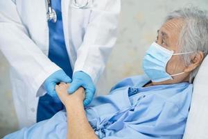 médico verificando paciente idoso asiático ou idosa senhora usando máscara facial no hospital para proteção contra infecção covid 19 coronavírus foto