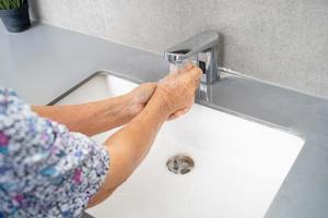 Paciente idoso asiático ou idosa lavando as mãos com sabão e água limpa para proteger a infecção segura e matar o novo vírus coronavírus covid 19 foto