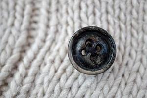 botão preto na lã branca foto